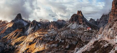 Living on the edge, literally. Touristic buildings waiting for the people who wants goes through these majestic dolomite mountains. Panoramic photo. 版權商用圖片 - 134791663