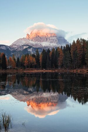 Vertical photo. Gorgeous mountains in clouds. Great landscape. Woods near the lake.
