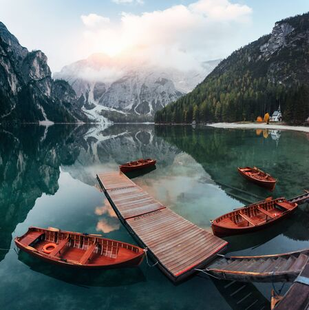 Chapel is on the other coast. Wooden boats on the crystal lake with majestic mountain behind. Reflection in the water.