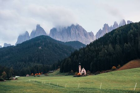 No people here. Farm with chapel near the forest. Majestic mountains at background. Stock fotó