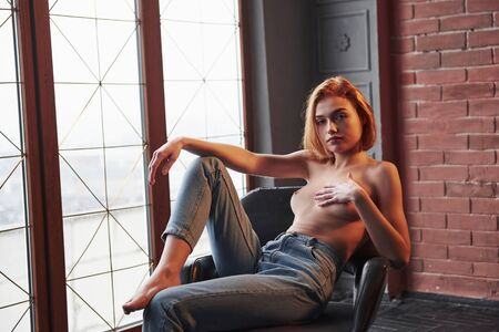 Natural breast. Girl sits on the chair. Half naked attractive young woman showing her hot body.