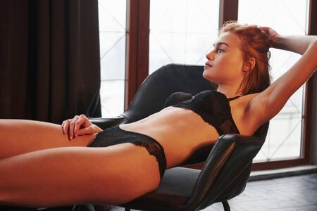 Enjoying the rest. Hot gorgeous young girl in underwear sitting on the chair indoors.