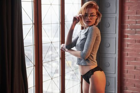 Touching the glasses. Desired look. Sexy blonde girl in eyewear, underwear and no bra under the shirt posing near the window in the room.