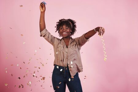 Happy like a child. Throwing the confetti in the air. African american woman with pink background behind.