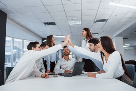 High five all. Job is done. Group of office workers happy to hit their own records and being successful.