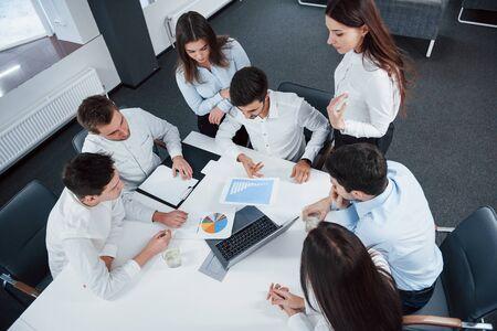Bovenaanzicht van kantoormedewerkers in klassieke kleding die bij de tafel zitten met laptop en documenten.