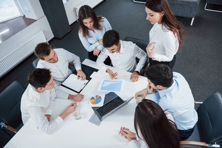 Top view of office workers in classic wear sitting near the table using laptop and documents.