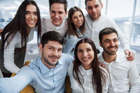 Foto dal telefono. Giovane squadra che fa selfie in abiti classici nell'ufficio moderno e ben illuminato.