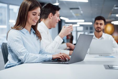 Woman type a text while guy behind have drink from silver glass. Side view of girl works on the silver colored laptop in the office and smiling. 스톡 콘텐츠