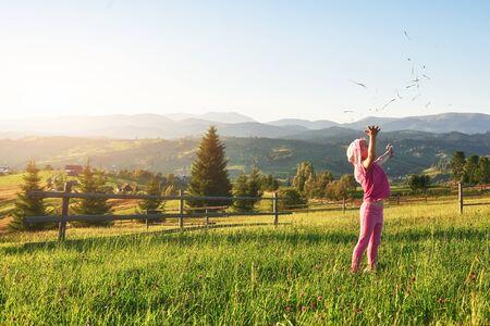 Linda niña feliz juega al aire libre temprano en la mañana en el césped y admira la vista de las montañas. Copie el espacio para su texto. Foto de archivo