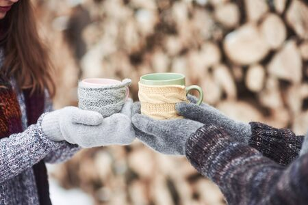 Couple hands in mittens take a mugs with hot tea in winter park.