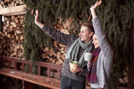 Photo of happy man and pretty woman with cups outdoor in winter. Winter holiday and vacation. Christmas couple of happy man and woman drink hot coffe. Hello neighbors!