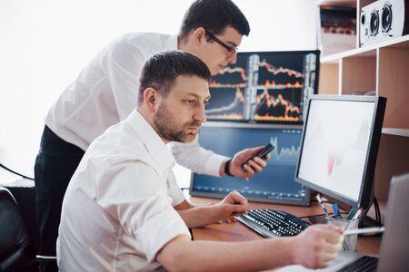 Hommes d'affaires négociant des actions en ligne. Courtiers en valeurs à la recherche de graphiques, d'index et de chiffres sur plusieurs écrans d'ordinateur Collègues en discussion au bureau des commerçants. Concept de réussite commerciale.