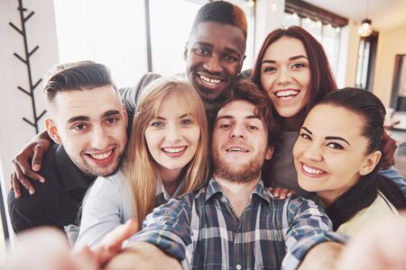 Friends having fun at restaurant.Two boys and four girls drinking making selfie, making peace sign and laughing. On foreground woman holding smart phone. All wear casual clothes.