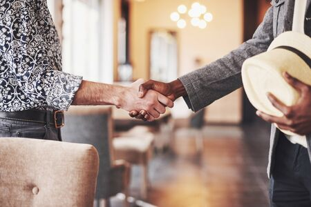 Black and white entrepreneurs shaking hands, satisfied multi-ethnic casual businessmen binding business deal with handshake, thanking for help support in successful teamwork. Stock Photo
