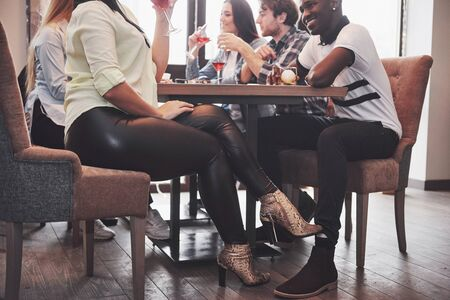 Girl flirting with a guy touching leg her foot under the table in a cafe while having fun with the friends. Flirt with your foot during lunch.