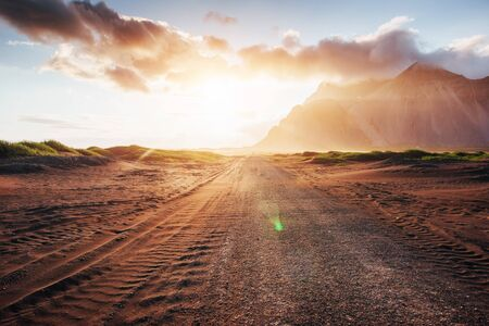 Fantastic sunset of the mountains and volcanic lava sand dunes to the beach in Stokksness. the concept of a hot day and a desert.