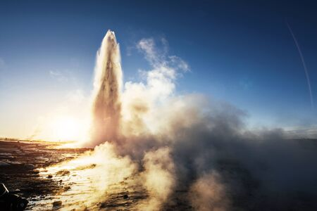 Eruption of Strokkur geyser in Iceland. Winter cold colors, sun lighting through the steam.