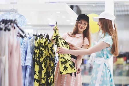 Young beautiful women at the weekly cloth market - Best friends sharing free time having fun and shopping. Stock Photo