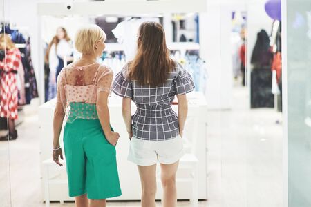 We should look at new dresses Rear view of two beautiful women with shopping bags looking away with smile while walking at the clothing store.