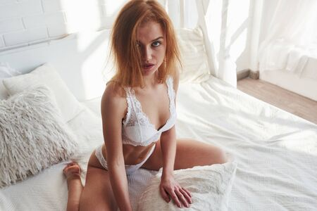 Hot woman. Portrait of a sexy redhead girl sitting on the bed and posing in the white room.