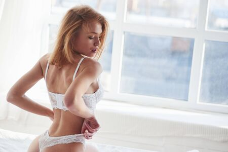 Seductive movements. Hot redhead girl in underwear sits on the white bed before the windows.