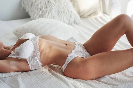 Close up view. Woman in white clothes lying on the bed with daylight comes from the window.