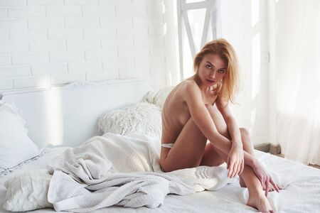 Full lenth view. Almost naked redhead girl covering her chest with legs and hands while sitting on the bed. Foto de archivo