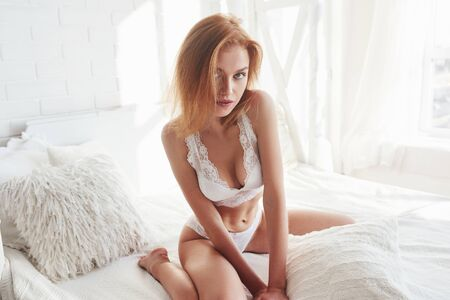 Nice ginger haired young woman. Portrait of a sexy redhead girl sitting on the bed and posing in the white room.