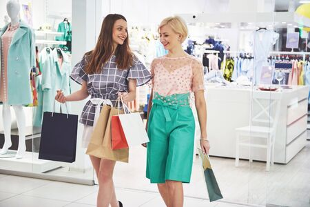 Great day for shopping. Two beautiful women with shopping bags looking at each other with smile while walking at the clothing store. 스톡 콘텐츠