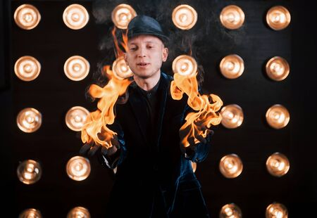 The fire is in his hands. Professional magician showing trick. Light bulbs on background.