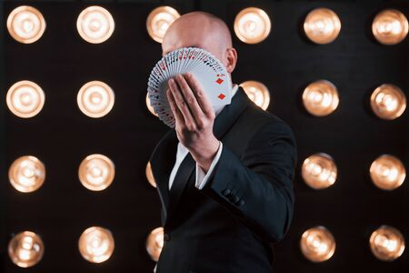 Focused photo on playing cards. Magician in black suit standing in the room with special lighting at backstage.