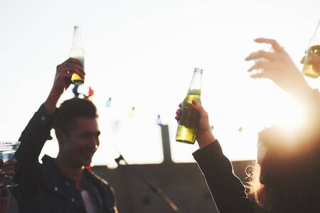 Hands in the air. Its rooftop party. Group of friends have holidays at sunny autumn day. Banco de Imagens