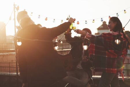 Guitar and alcohol. Its rooftop party. Group of friends have holidays at sunny autumn day. Banco de Imagens