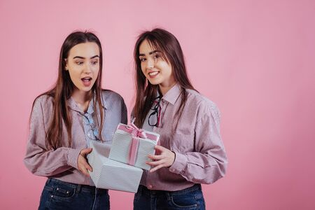 Its holiday presents. Two sisters twins standing and posing in the studio with white background.