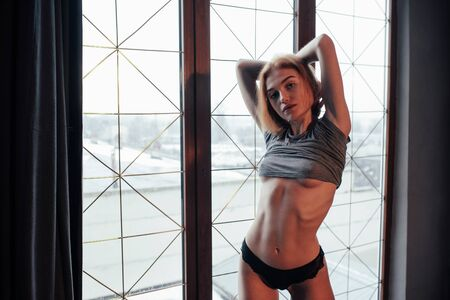 Seductive young woman. Sexy blonde girl in underwear and no bra under the shirt posing near the window in the room.