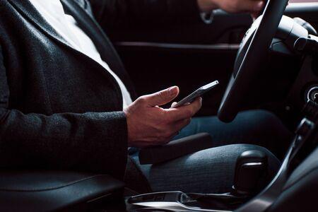 Rijke kleding, auto en mobiel apparaat. Werken in de auto met behulp van zilverkleurige smartphone. Hogere zakenman. Stockfoto