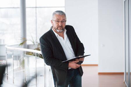 Lugar de aspecto moderno. Foto de empresario senior en la espaciosa habitación con plantas detrás. Sostener y leer documentos. Foto de archivo