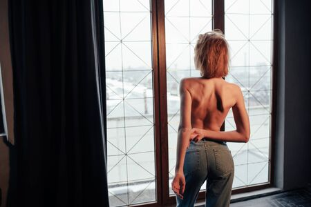 Natural and artificial lighting. Hot young blonde with bare chest and jeans stands against the window.