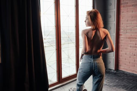 View from behind. Hot young blonde with bare chest and jeans stands against the window.