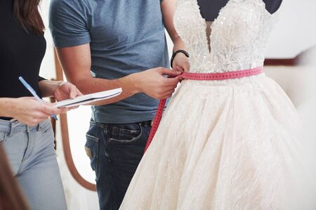 Man measure waist of mannequin. The process of fitting the dress in the studio of hand crafted clothes.