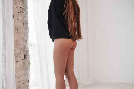 Only lower part. Hot girl in black wear stands in the room against white wall. Stock Photo