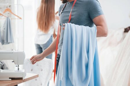 Guy takes needed tools and material. The process of fitting the dress in the studio of hand crafted clothes.