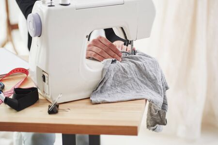 Womans hands on job. Female fashion designer works on the new clothes in the workshop.