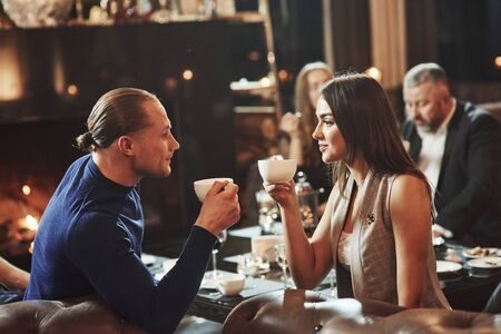 Drinking tea and looking at each other. Beautiful couple. Family friends having nice time in beautiful luxury modern restaurant. Reklamní fotografie