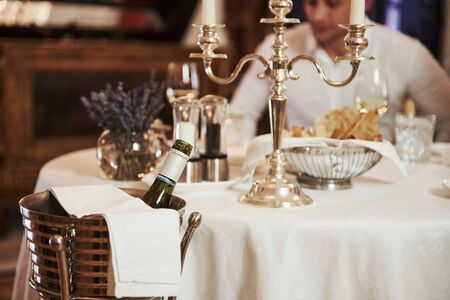 Man in white shirt on background. Close up view of served table with bottle of champagne.