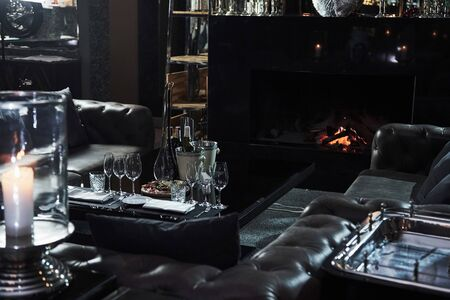 Calm place in the restaurant with table full of champagne glasses and beautiful fireplace.