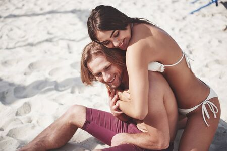 A romantic couple on the beach in a swimsuit, beautiful sexy young people.
