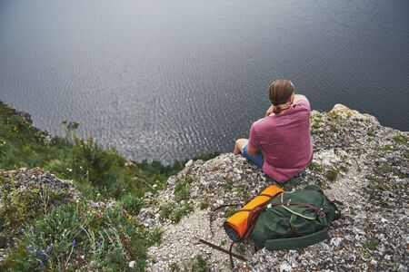 Traveller with backpack sitting on top of mountain enjoying view above the water surface. Traveling along mountains and coast, freedom and active lifestyle concept.