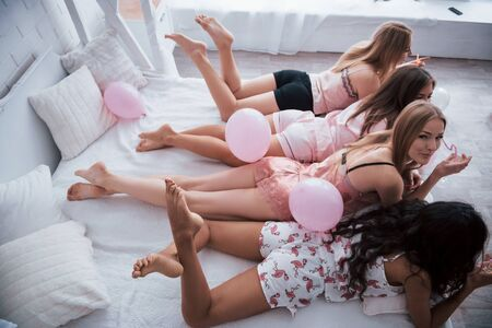 Holding a drinks. Young girls lying on luxury white bed have celebrating. Side and top view.